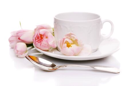 Tea cup with pink tulips on white background photo