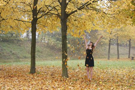 giggle: laughing woman in black dress throwing leaves in the air