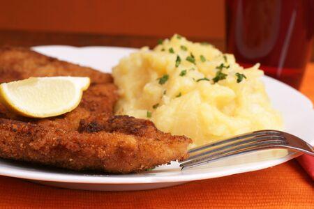 Wiener Schnitzel with potato salad topped with chopped chives. Stock Photo