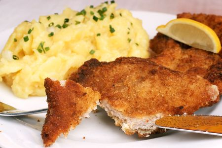 Wiener Schnitzel with potato salad topped with chopped chives. Reklamní fotografie