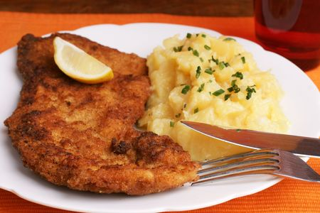 wiener: Wiener Schnitzel with potato salad topped with chopped chives. Stock Photo