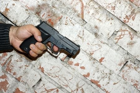Crime concept. Hand holding a pistol in front of brick  wall. photo