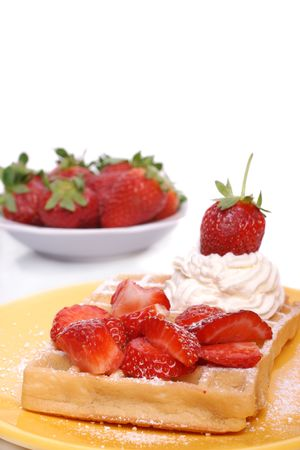 Waffle on plate with strawberries and whipped cream.