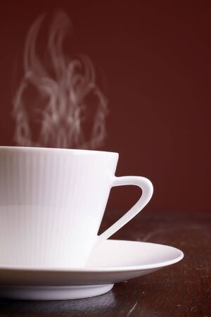 coffe break: Cup of steaming hot coffee over dark background. Stock Photo