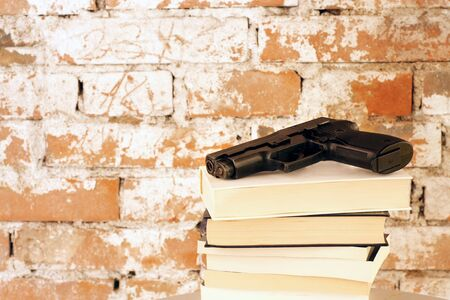 Crime Story: Handgun on top of stack of books