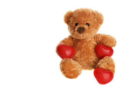 Toy teddy bear with red hearts isolated over white. photo