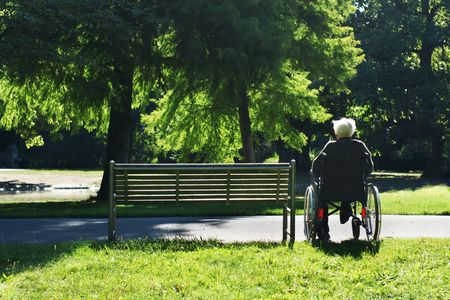 healthcare facilities: Lonely elderly man sitting in a wheelchair next to a bench. Stock Photo
