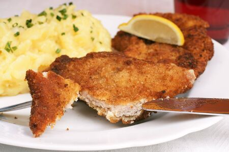 Wiener Schnitzel with potato salad topped with chopped chives. photo
