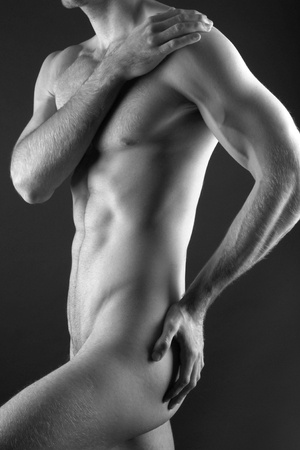 Young muscular nude man over black background