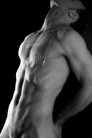 hombre desnudo: El hombre con el torso muscular sobre fondo negro Foto de archivo