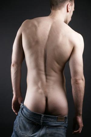 Hombre desnudo bajando los pantalones vaqueros y mostrando el culo Foto de archivo - 11836852