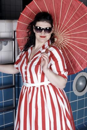 Pretty woman wearing a summer dress posing in pool