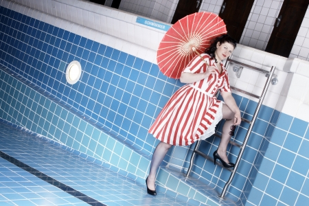 Pretty woman wearing a summer dress posing in pool photo