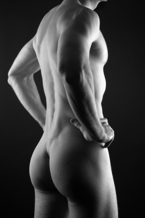 Young muscular sporty man over black background