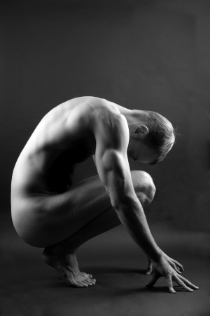 nude man: Young muscular nude man over black background