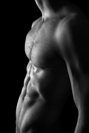 desnudo masculino: Joven deportivo con gotas de agua en la piel sobre el negro