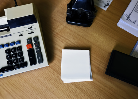 Retro calculator, paper punch and note pad.