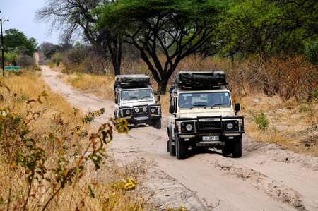 Two jeeps drive along a sandy track in Chobe National Park in Botswana.