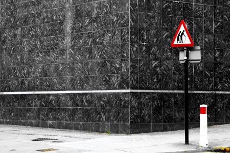 Danger senior crossing sign on an empty road corner Banco de Imagens