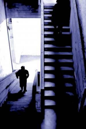 descend: Shadows and lights of men who climb or descend stairs in a surreal building Stock Photo
