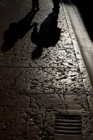 dirty hands: Shadow of two lovers holding hands reflected on a pavement in the sunset light