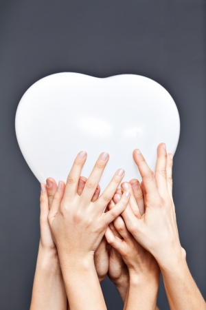 Multiple hands are holding a heart balloon photo