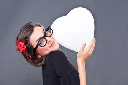 lolita: Little lolita girl is smiling while holding a heart balloon