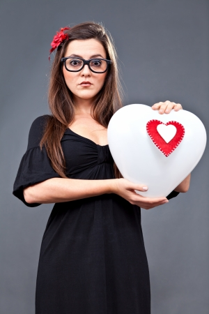 Little lolita girl standing with a heart balloon in her hands photo