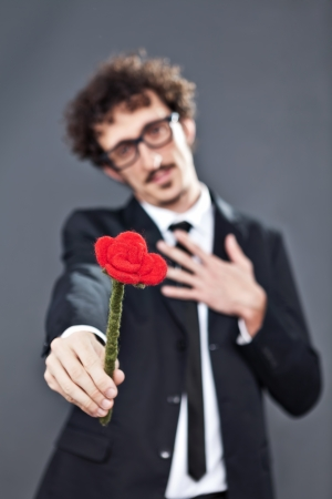 Boy with glasses is donating a fabric red rose photo