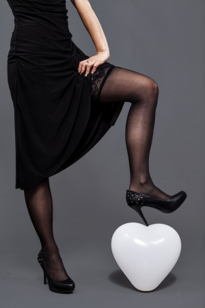 girl with lace pantyhose crushes with her shoe an heart shape balloon photo