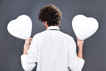Man is holding two heart balloons while facing on his back photo
