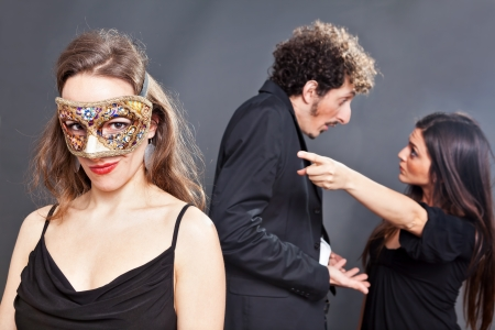 betray: Man is caught red-handed with another masked girl  Stock Photo