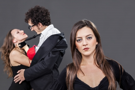 betray: girl is sadly looking while her boyfriend flirts with another woman
