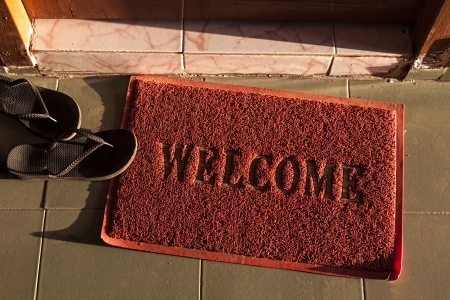 a red welcome doormat next to a couple of black flip flops is illuminated by a lateral sunrise light Banco de Imagens