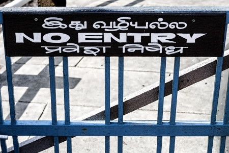 a wooden sign affixed above a wooden gate shows in English and Asian language the prohibition of entry to a path Stock Photo - 20171770