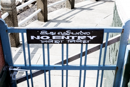 affixed: a wooden sign affixed above a wooden gate shows in English and Asian language the prohibition of entry to a path Stock Photo