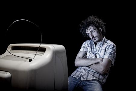 sedentario: un hombre se está aburriendo mientras ve la televisión solos Foto de archivo