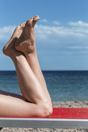 Bare feet of a young girl lying on a deck chair on a beach photo