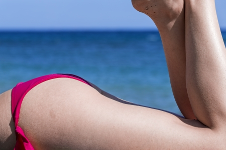 female ass: Close up of a female ass that wear a fuxia swimsuit Stock Photo