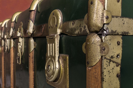 Detail of the golden locks and hinges of a green trunk with wooden inserts photo