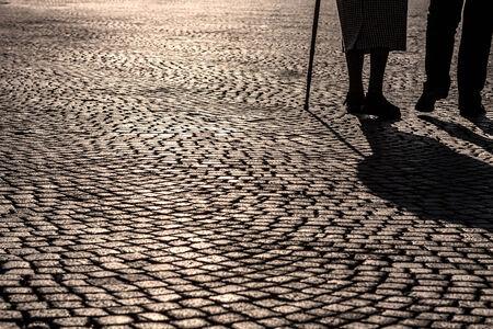 Silouette and shadow of legs of elderly pedestrians couple in a cobblestone square Banco de Imagens