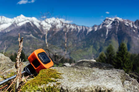 Action camera is resting against a rock, with a mountain panorama as background