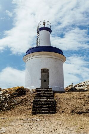 White and blue lighthouse on a cape, surronded by clouds Banco de Imagens