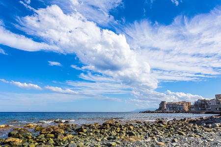stones beach in a bay with a tower and a village on its pier and stormy clouds in the sky Banco de Imagens
