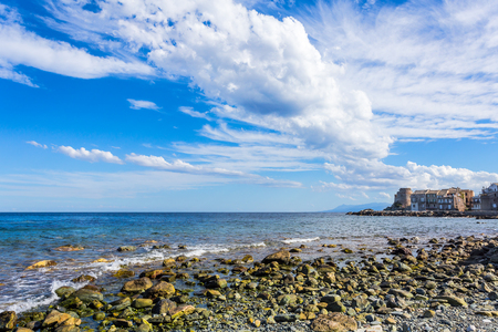 stones beach in a bay with a village on its pier and stormy clouds in the sky Banco de Imagens