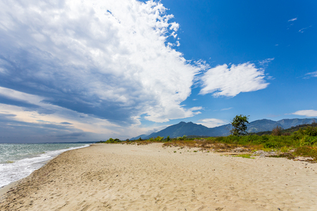 A wild beach near a mountainous landscape with close vegetation with stormy clouds above Banco de Imagens