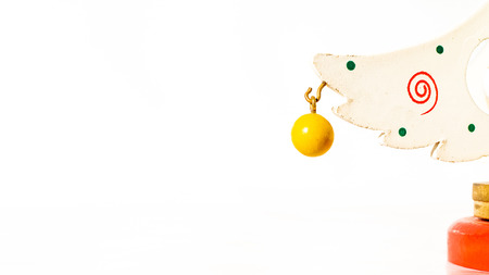 Christmas white ticket decorated with a wooden yellow ball hanging on a branch of a wooden toy Christmas tree Banco de Imagens