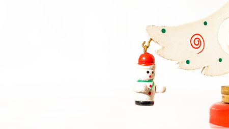 Christmas white ticket decorated with a wooden snow puppet hanging on a branch of a wooden toy Christmas tree