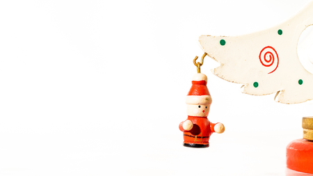 Christmas white ticket decorated with a wooden santa claus hanging on a branch of a wooden toy Christmas tree