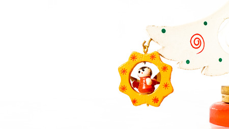 Christmas white ticket decorated with a wooden angel hanging on a branch of a wooden toy Christmas tree